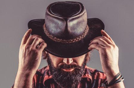 American cowboy. Leather Cowboy Hat. Portrait of young man wearing cowboy hat. Cowboys in hat. Handsome bearded macho. Man unshaven cowboys Reklamní fotografie
