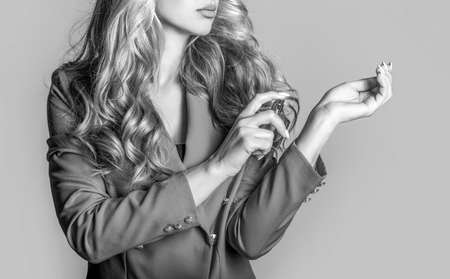 Beautiful girl using perfume. Woman with bottle of perfume. Woman presents perfumes fragrance. Perfume bottle woman spray aroma. Woman holding a perfumes bottle. Black and white