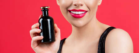 Beautiful girl using perfume. Woman with bottle of perfume. Woman presents perfumes fragrance. Woman perfumes bottle. Sexy lips. Red lip