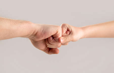 Two hands: man and child. Father and son touching fists. Old man and kid holding hands together. Little and big fists of father and son. Mother and kid daughter are fist bumping