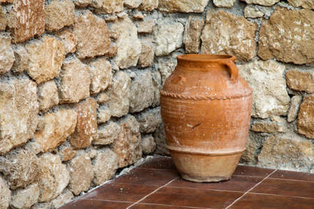 Decorative clay pot in the front of a stone wall
