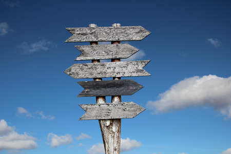 Wooden signpost against a blue sky as a background