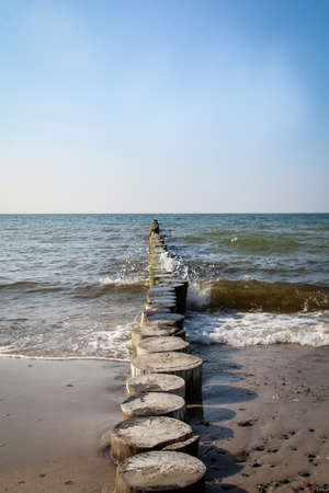 Wooden piles (groynes) that rise from the sands of the Baltic sea protect the beach and the coast Standard-Bild - 122879384