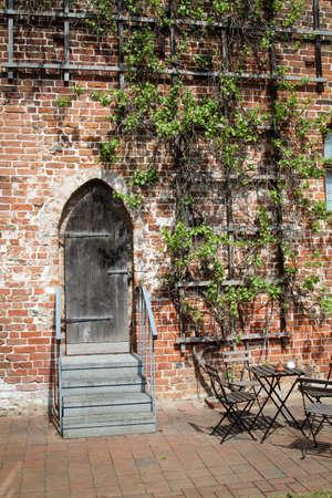 A rustic wooden door against a brick wall