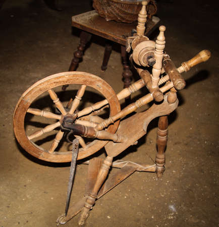 An old wooden spinning wheel was spun on the wool