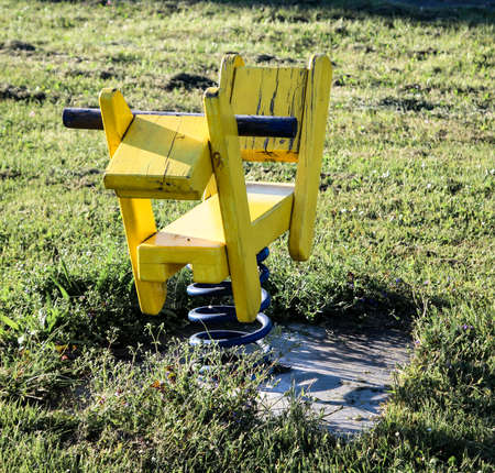 A yellow rocking horse for children on a playground