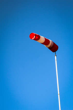 Airport windsock on clear blue sky background in windy weather