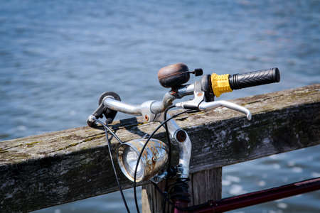 Detail of a bicycle, the handlebar of a wheel with a bell and a bicycle lamp Stockfoto