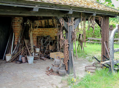 Looking under the canopy of an old forge with all sorts of chains and iron objects