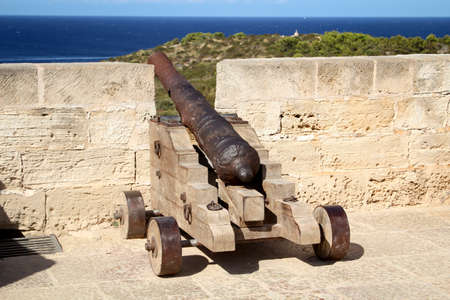 A medieval cannon at a harbor basin Stock Photo