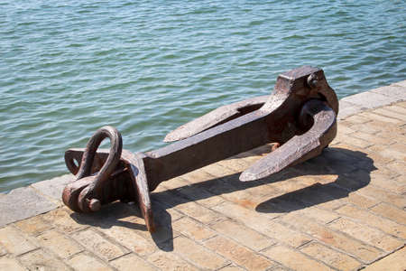 Detail view of a huge old anchor at the harbor basin