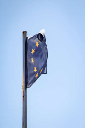 A Europe flag fluttering on the flagpole in the wind