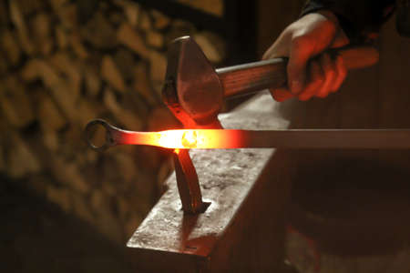 A blacksmith uses a hammer to work a glowing piece of metal on the anvil Archivio Fotografico