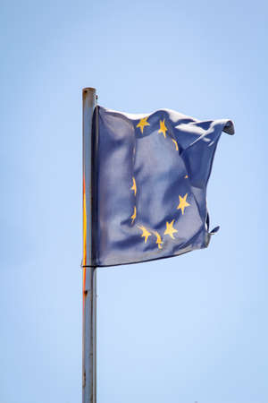 A euro flag flutters in the wind against a blue sky
