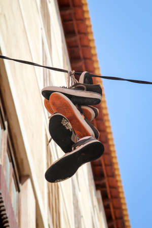Several pairs of shoes tied together hang on a power line Reklamní fotografie