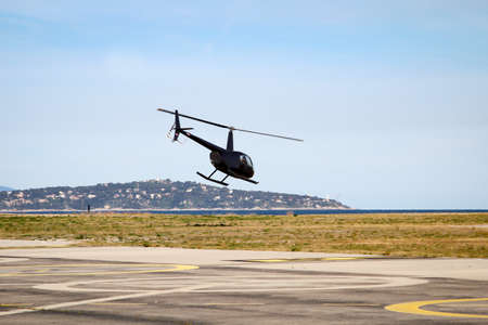 A helicopter with two main rotor blades at takeoff