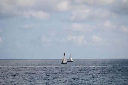 Two sailing boats compete on the Mediterranean.