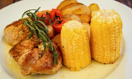 A plate of meat, corn on the cob and potato wedges.