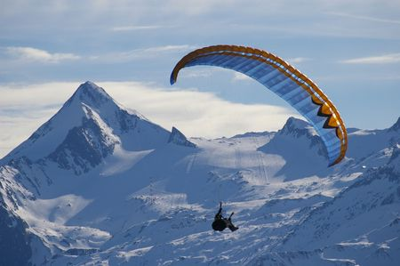 Paragliding over mountain in winter Stock Photo