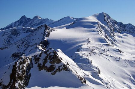 Mountain ridge in Alps, blue sky and lots of snow Stock Photo