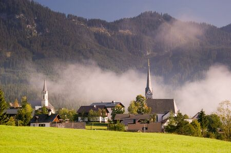 Church in fog in dramatic morning light in an typical austrian village