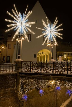 winter snow christmas lights on street and bridge in Sibiu in winter long exposure image by night with public lighting and specific decoration  photo