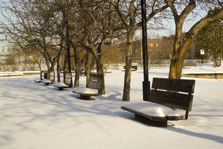 frostily: winter park bench untouched snow city during hard season sunny day Stock Photo