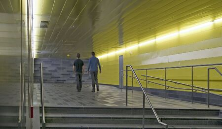 people walking in underground tunel neon lights yellow reflecting wall Stock Photo