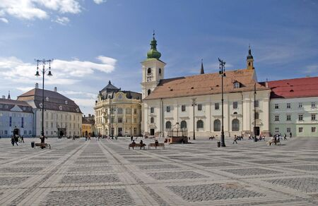 main square historical arhitecture in Sibiu Transylvania Romania catholical church public lantern and Brukenthal palace in background