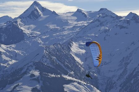 winter paragliding in alps mountains over high peaks and valley