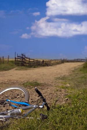 mountain bike resting down on side of gravel country road on beautiful summer day Stock Photo