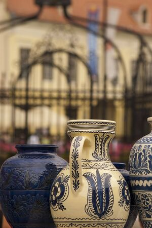 colored traditional pottery in Sibiu on display with old houses in background