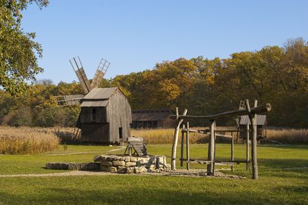 spectacular old wooden woodmill and water fountain behind cane on a beautiful autumn day with blue sky Stock Photo