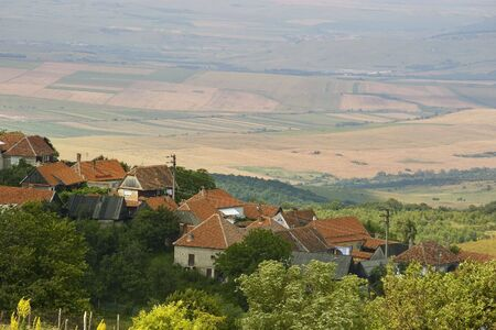 mountain village Jina in Transylvania Romania on hill top with highland cultivated land in background