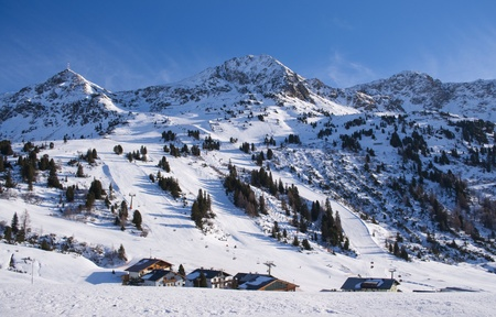 Ski slope and chalets houses in touristic resort Obertauern in Austrian Alps mountain range in Austria
