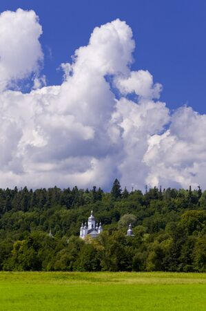 Church tower in middle of forrest on summer day Stock Photo