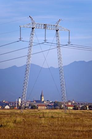 Electricity pylon and Sibiu city with Fagaras mountain range in background Stock Photo - 10795384