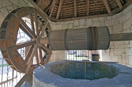 water well with wheel at old castle Khotyn in Ukraine Stock Photo
