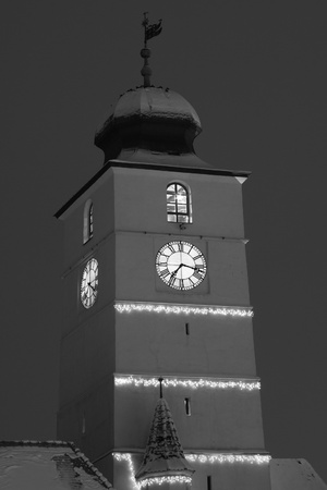 christmas and new year lights decorated architecture clock tower Sibiu Transylvania Romania, black and white desaturated image photo