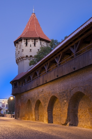 Sibiu, Romania - medieval 14th century fortification tower and wall in old town at twilight