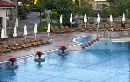 Swimming pool with deckchairs at luxury hotel