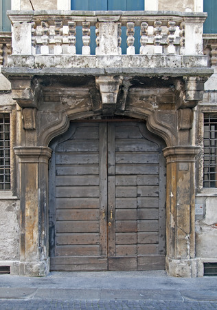 decayed: Decayed dooden door on ruined stone facade Stock Photo