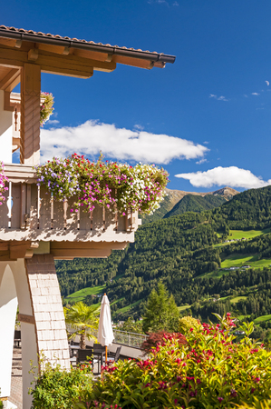 Balcony flowers on a traditional alpine house in Alps mountains, beautiful summer day