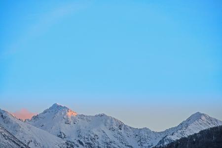 Last rays of sun at winter sunset on mountain ridge (Carpathians, Negoiu peak, second highest in Romania 2535 meters) Stock Photo