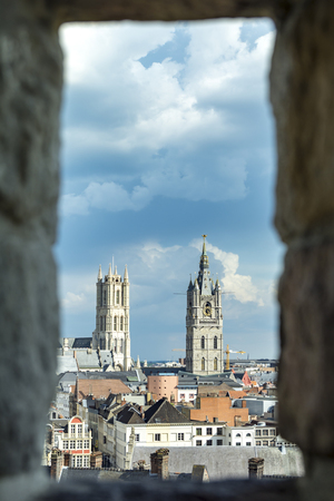 Cityscape in old town Gent of Belgium, belfry and St Bavo cathedral view through arrowslit from Gravensteen castle