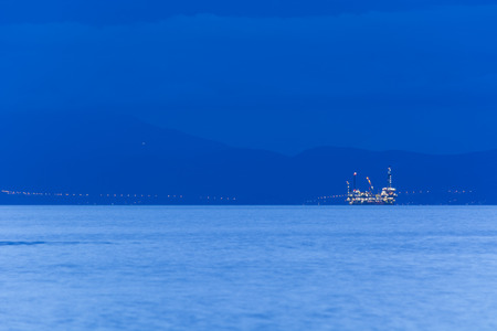 Big offshore oil rig drilling platform complex with anchored ship at dusk, with continent in background, Aegean Sea, Greece