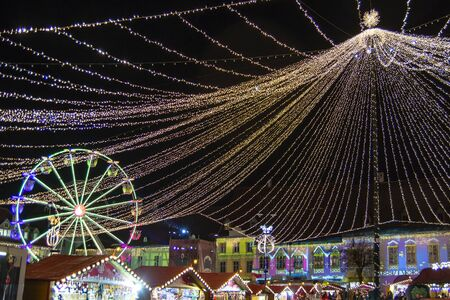 Christmas market decoration lights (projection video mapping on buildings) and amusement wheel in Sibiu main square, Transylvania, Romania