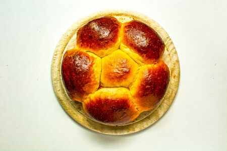 Brioche filled with jam, traditional european dessert on wooden plate