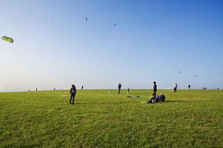 people on a grassland in october with their kites ### Wiese mit Leuten beim Drachen steigen lassen
