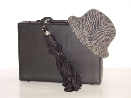 Black briefcase, in vertical position, with black umbrella and hat, isolated. (stock photo) Stock Photo